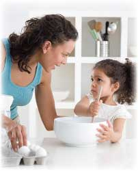 mother teaching child in kitchen